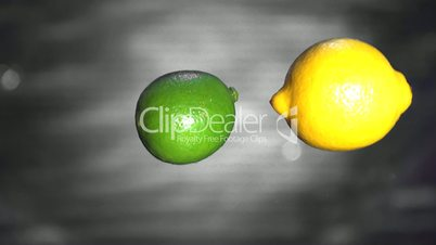 Lemon and lime falling into water close up