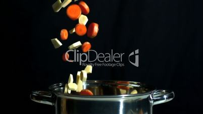 Sliced carrot and parsnip falling into saucepan on black background