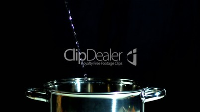 Water flowing into saucepan on black background