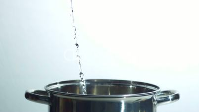 Water flowing into saucepan on white background