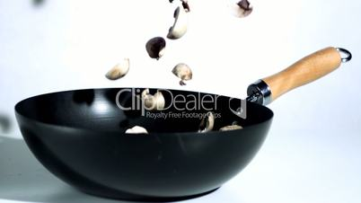 Mushrooms falling into wok