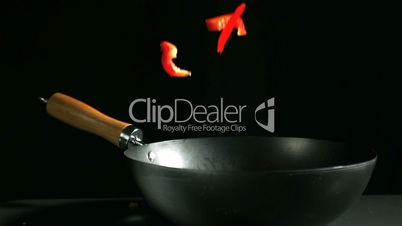 Sliced red pepper falling into wok on black background