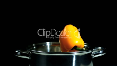 Yellow pepper falling into pot