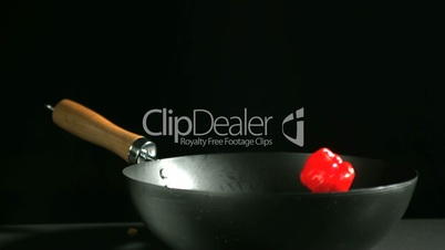 Red scotch bonnet chili falling into a wok
