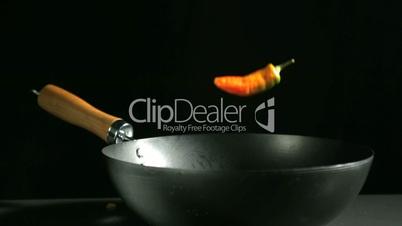 Jalapeno chili falling into a wok