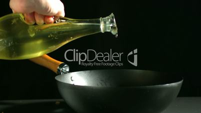 Olive oil being poured into wok