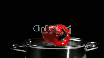 Red pepper falling into a pot