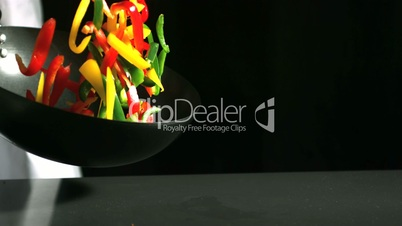 Chef tossing wok of peppers