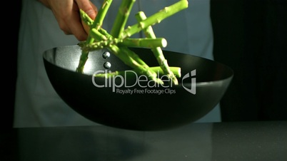 Chef tossing wok of asparagus