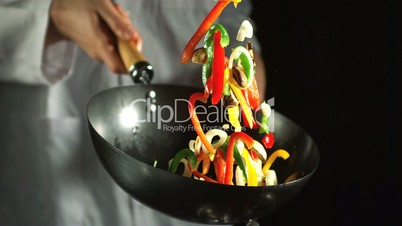 Chef making vegetable stir fry in wok
