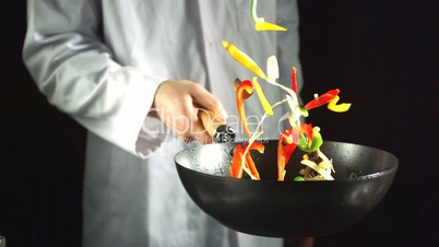 Chef tossing vegetable stir fry in a wok