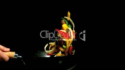 Chef tossing vegetables in wok side view