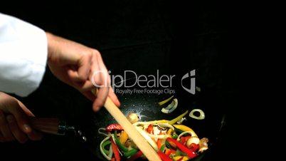 Chef stirring vegetables in wok