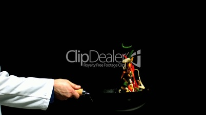 Chef tossing vegetables in a wok side view on black background