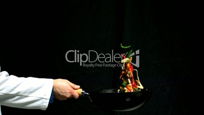 Chef tossing vegetables in a wok black background