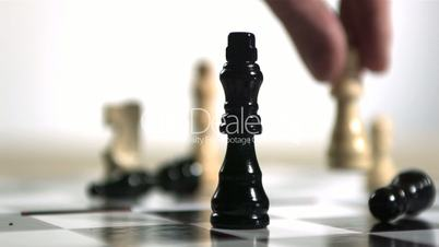 Hand knocking over black chess piece with white one