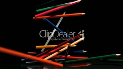 Colouring pencils falling on black background