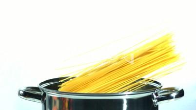 Spaghetti falling in a pot