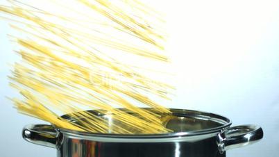 Spaghetti falling into a saucepan