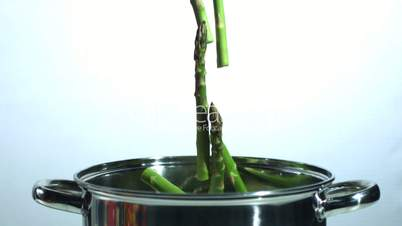 Asparagus stalks falling into a saucepan