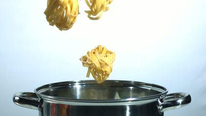 Tagliatelle falling into a saucepan