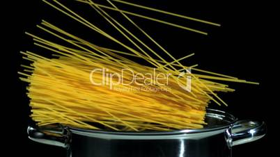 Spaghetti falling in pot on black background