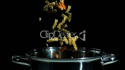 Fusilli falling in pot on black background