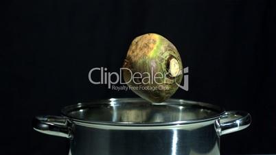 Turnip falling in saucepan on black background