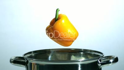 Yellow pepper falling in saucepan