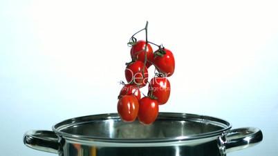 Vine tomatoes falling in saucepan