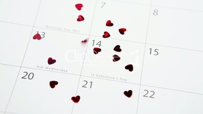 Heart confetti falling on calendar on highlighting valentines day