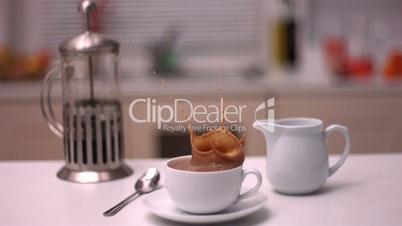 Sugar cube falling in coffee