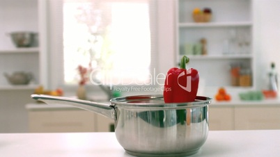 Red pepper falling in saucepan in kitchen