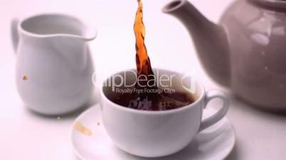 Cube of sugar falling in tea cup