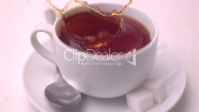 Sugar cube falling into tea and splashing