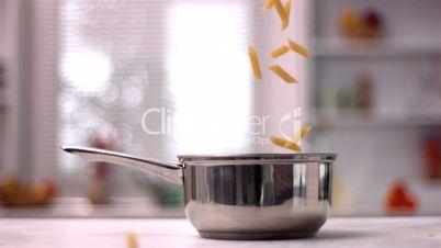 Penne falling in pot in kitchen