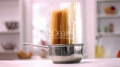 Spaghetti falling in a saucepan in kitchen