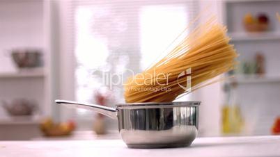 Spaghetti falling in saucepan in kitchen