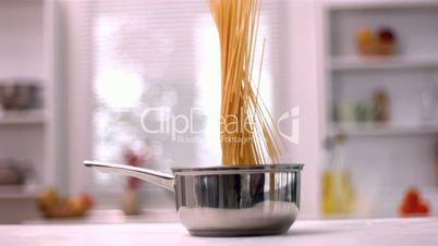 Spaghetti falling into pot in kitchen