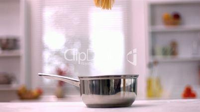 Spaghetti falling in a pot in kitchen