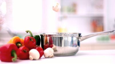Mushrooms falling into a saucepan in kitchen