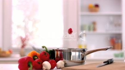 Cherry tomatoes and mushrooms falling in saucepan in kitchen