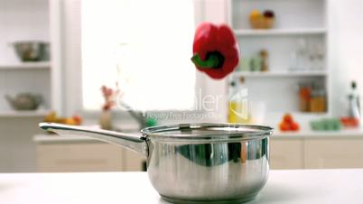 Red pepper falling into saucepan in kitchen