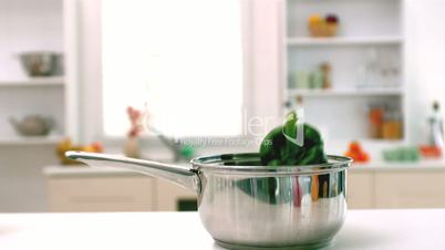 Green pepper falling in saucepan in kitchen