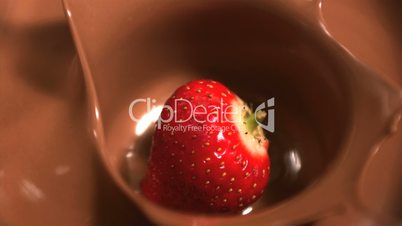 Strawberry falling into melted chocolate close up