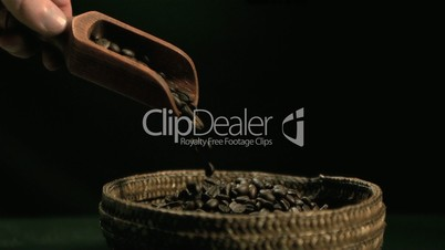 Hand pouring coffee beans from wooden spoon to basket