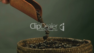 Hand pouring coffee beans from wooden spoon into basket