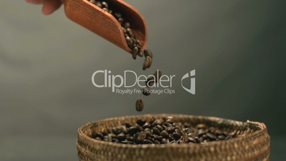 Hand pouring coffee beans from a wooden spoon into basket