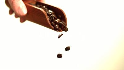 Hand pouring coffee beans from wooden spoon