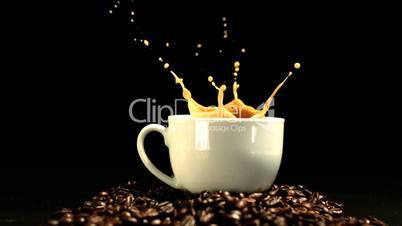 Sugar cube falling in coffee cup and splashing